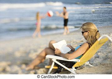Mom reading book on beach.