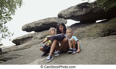 Mom reads a book to her children in the mountains