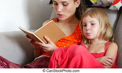 Mom reads a book to her daughter