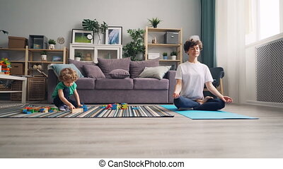 Mom relaxing in lotus position while calm child playing with toys wooden blocks