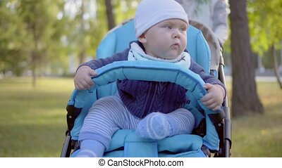 Mom rolls toddler in a stroller. Baby smiling and looking around . Outdoor.