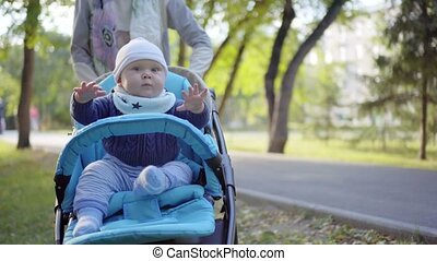 Mom rolls toddler in a stroller. Baby waving his arms. Outdoor.