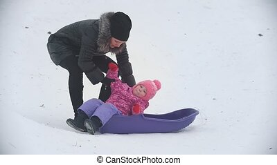 Mom seating his disobedient daughter in sled on winter...