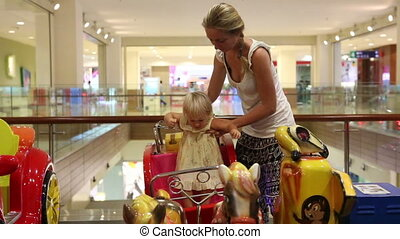 Mom sits down her daughter in the toy chariot on playground...