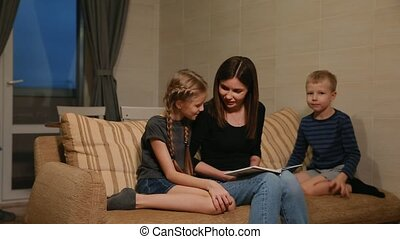 Mom sitting on the couch with his daughter and young son,...