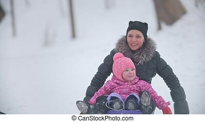Mom slithering her little pretty daughter on a sled in a...