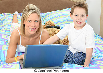 Mother and son with laptop in bed.