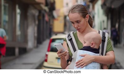 Mom stands on the street with a child in a sling and looks at the mobile phone screen
