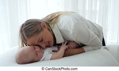 mom stroking a newborn baby lying