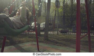 Mom swinging a kid on a swing in the courtyard. 4K