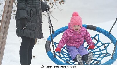 Mom swinging her cute little daughter on a swing on the...