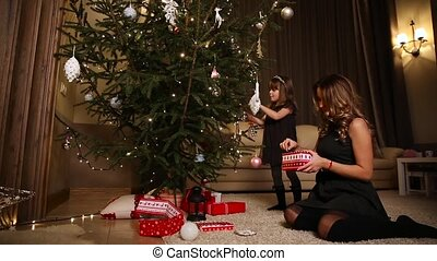Mom takes out Christmas decorations from the box, passing them to his daughter to paint a Christmas tree.
