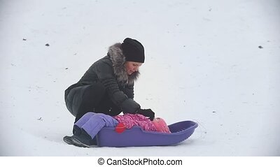 Mom talking with her little daughter, who lying in a sled in the winter park