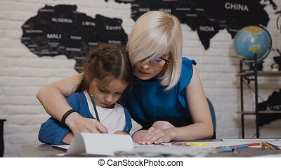 Mom teaches her daughter to write first letters. Teacher and student perform homework in elementary school. Young blonde teacher and her brunette little daughter sit at the desk in the classroom and write a pencils on paper. Close-up