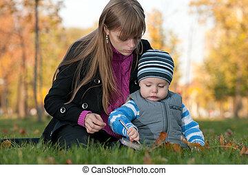 Mom teaches her son in the autumn park