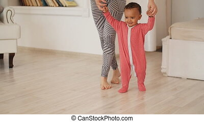 Mom teaches her son to walk. Mixed race baby
