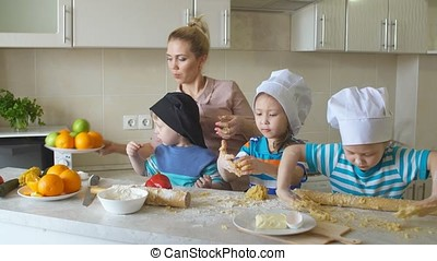 mom teaches kids to cook. children kneading dough in the...