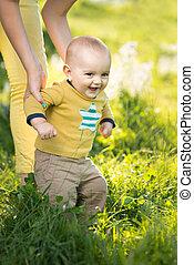 Mom teaches son walking grass