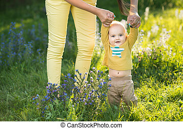 Mom teaches son walking grass