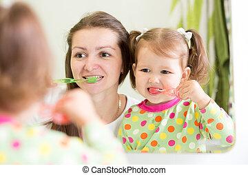 mom teaching child teeth brushing