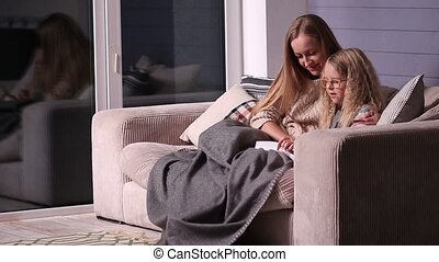 Mom teaching daughter to read at home