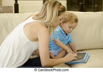 Mom teaching her son to use tablet