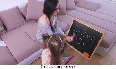 Mom teaching little girl