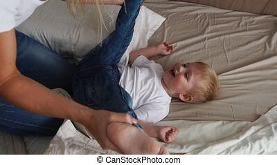 Mom tickles the boy lying on the bed who looks directly into...