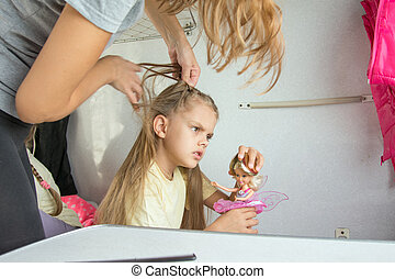 Mom tries to unravel the tangled hair girl in a train