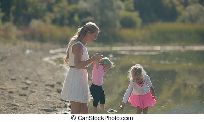 Mom walks with her little cute girls near lake