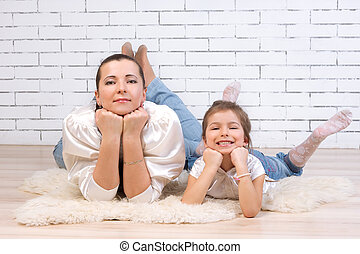 Mom with 5 year old daughter lying on the floor