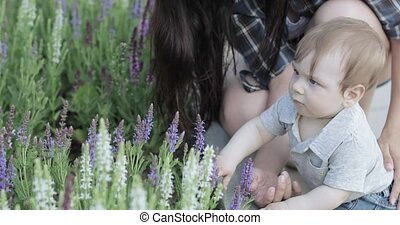 Mom with a child near a flower bed