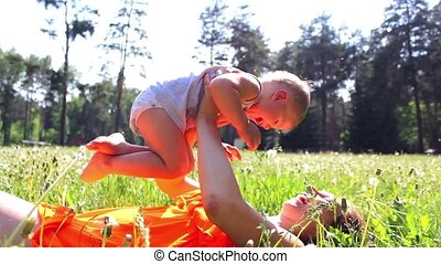 Mom with a child playing on meadow in the park