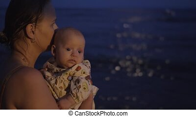 Mom with baby on the beach at night