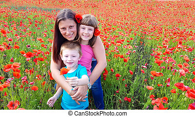 mom with children in a field of poppies