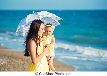 Mom with daughter under a white lace umbrella on a hot day