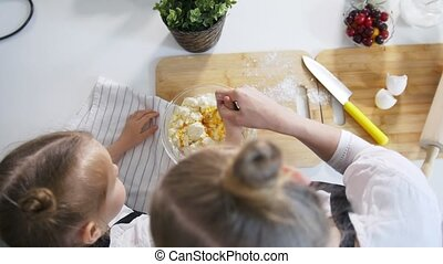Mom with her daughter makes dough for cottage cheese pancakes - top view