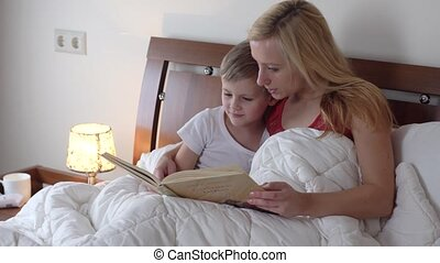 mom with kid reading book in bed