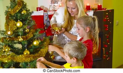 mom with kids decorating christmas tree