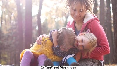 Mom with little girls on a picnic in the autumn forest