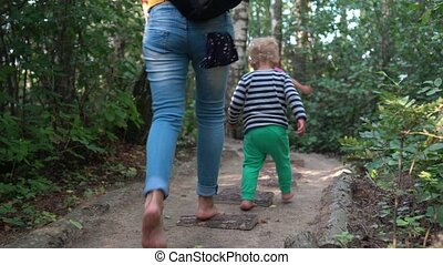 Mom with little son and daughter walking on healthy barefoot path