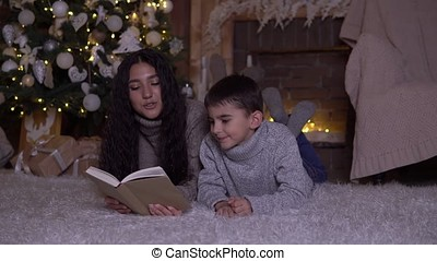 Mom with long hair reads a book to her son and kisses him lying on the floor near the Christmas tree on Christmas day. 4K