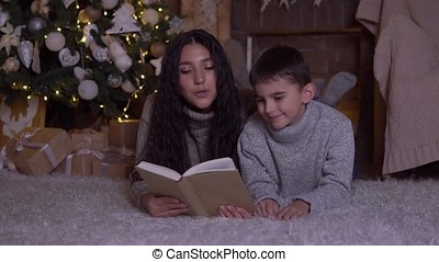 Mom with long hair reads a book to her son and kisses him lying on the floor near the Christmas tree on Christmas day.HD