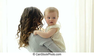 mom with long hair with her daughter in her arms standing