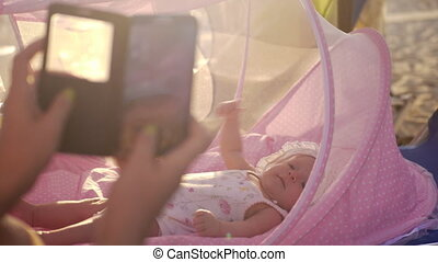 Mom with mobile taking picture of baby in bassinet outdoor -...