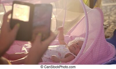Mom with mobile taking picture of baby in bassinet outdoor