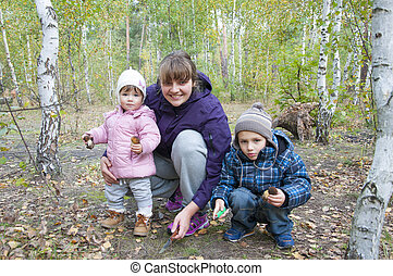 Mom with son and little daughter in the autumn birch forest are holding mushrooms.