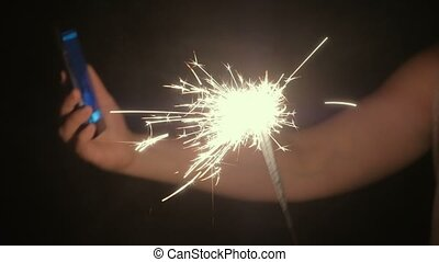 Mom with son are doing selfie with sparkler in sons hand. Family photo on the phone