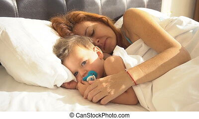 mom with son baby woke up in the morning on the bed