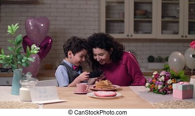 Mom with son watching funny video on smart phone